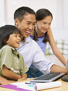 Father with son and daughter at a computer